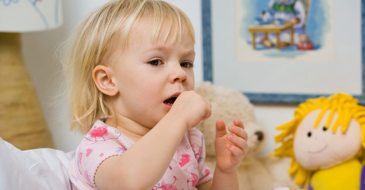 Tusea la bebelusi: Fetita mica, stand in pat, inconjurata de jucarii, tusind
