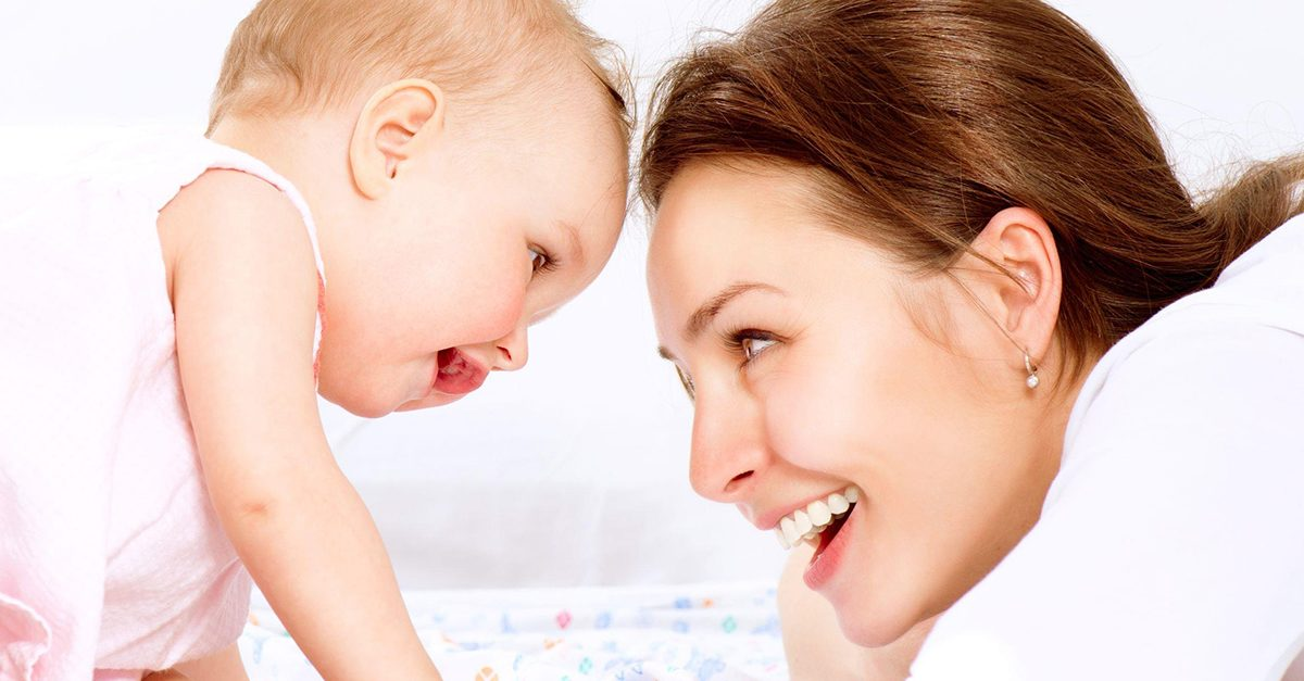 Mama si bebelusul se privesc si isi zambesc